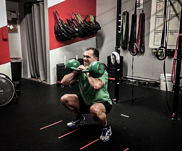 Man doing squats with two kettlebells at the 3Strong gym